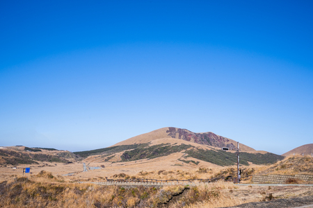 Aso mountain and dry brown grassland with miscanthusm in autumn, blue sky. Stok Fotoğraf - 113766381