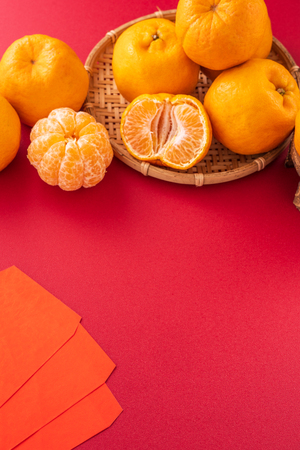 Beautiful and delicous tangerine isolated on red background with bamboo sieve, new modern auspicious and jubilant concept of chinese new year, close up, copy space Stock Photo