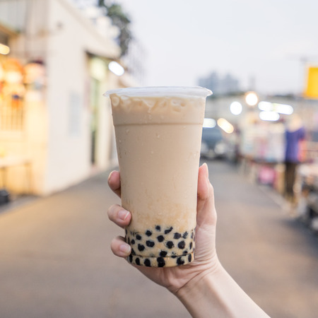 A young woman is holding a plastic cup of brown sugar bubble milk tea at a night market in Taiwan, Taiwan delicacy, close up. Stockfoto