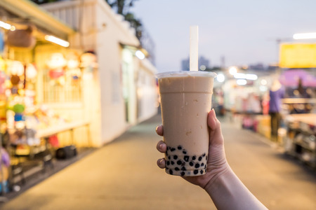 A young woman is holding a plastic cup of bubble milk tea with a straw at a night market in Taiwan, Taiwan delicacy, close up. Foto de archivo - 114113764