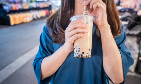 A young woman is drinking a plastic cup of bubble milk tea with a straw at a night market in Taiwan, Taiwan delicacy, close up. Imagens