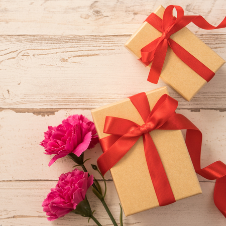 gift box with red ribbon bow and carnation, concept of giving present at mothers day as surprise, flat lay, top view