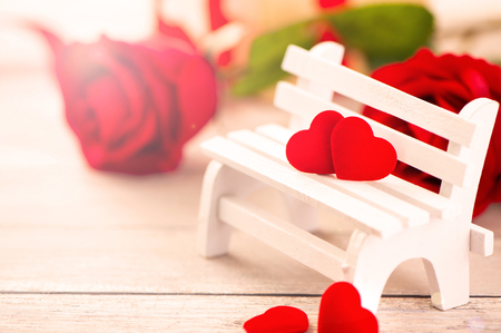Concept of Valentine, anniversary, wedding celebration, heart shapes on a white wooden bench, bokeh background, close up