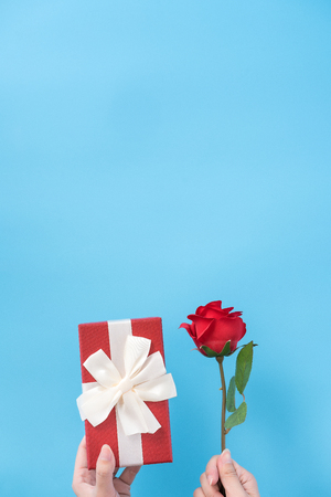 A young woman is giving a gift with greeting on blue background, concept of holiday and celebrate for festival surprising, copy space, topview Stock Photo