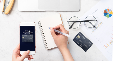 Concept of a woman is doing a online purchase, mock up card and cellphone on office desk isolated on beautiful fashion marble background, copy space, top view, flat lay, closeup Фото со стока
