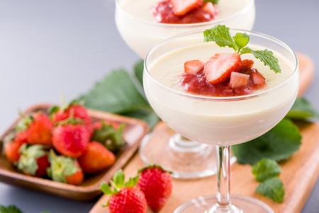 Desserts à la fraise double couleur (couleur) délicieux et nutritifs avec garniture de menthe et de sarcocarpe en dés isolés sur fond bleu aéré, espace pour copie, gros plan Banque d'images