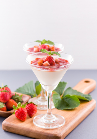 Delicous and nutritious double color (colour) strawberry desserts with mint and diced sarcocarp topping isolated with airy blue background, copy space, close up