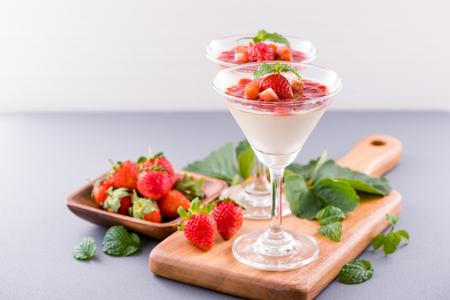 Desserts à la fraise double couleur (couleur) délicieux et nutritifs avec garniture de menthe et de sarcocarpe en dés isolés sur fond bleu aéré, espace pour copie, gros plan