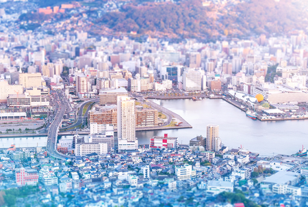 Business concept, tilt shift effect modern cityscape of nagasaki dusk from mount inasa, the new top 3 nightview of the world, aerial view, copy space