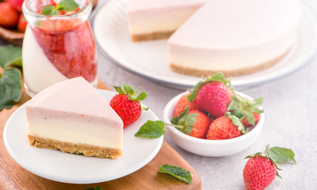 Delicious and nutritious handmade strawberry no bake frozen gradient colour fromage frais cheesecake slice with raw sarcocarp besides isolated with fair-faced gray background, copy space, close up