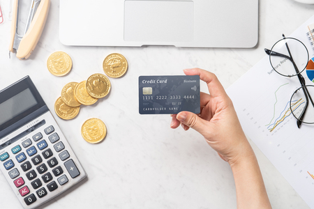 concept of a woman doing online payment with card and smartphone isolated on a modern marble office table, mock up, top view, copy space, flat lay, lifestyle, close up Imagens