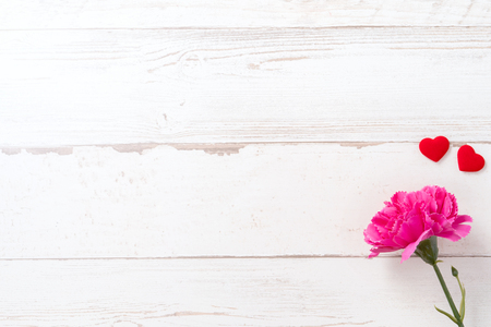 May mothers day concept photography - Beautiful carnations and hearts shape with white empty card isolated on a bright wooden table, copy space, flat lay, top view, mock up