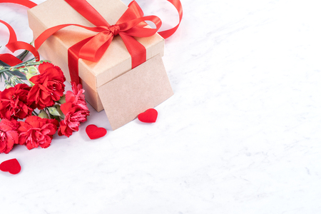 May mothers day concept handmade giftbox idea wishes photography - Beautiful blooming carnations with red ribbon bow box isolated on modern marble desk, close up, copy space, mock up Stock Photo
