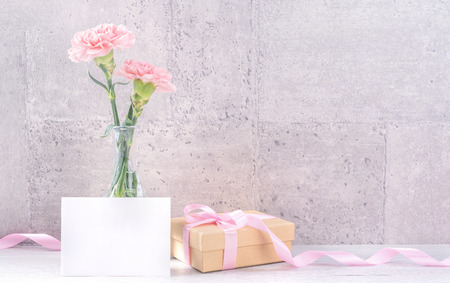 Mooie bloeiende anjers met roze lintdoos die op eerlijk grijze achtergrondbureau wordt geïsoleerd