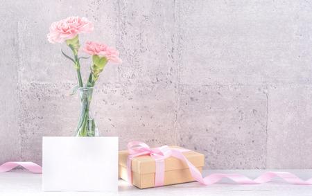 Piękne kwitnące goździki z różową wstążką na białym tle na jasnym szarym tle biurka