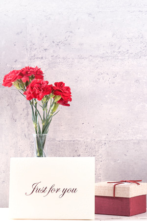 May mothers day handmade giftbox wishes photography - Beautiful blooming carnations with red ribbon box isolated on fair-faced gray background desk, close up, copy space, mock up