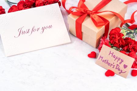 Foto de deseos de caja de regalo hecha a mano del día de las madres de mayo - Hermosos claveles en flor con caja de lazo de cinta roja aislada en el escritorio de mármol moderno, de cerca, espacio de copia, maqueta