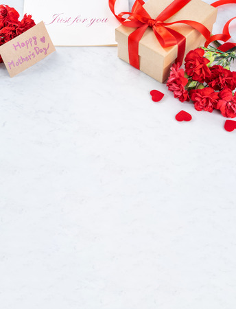 May mothers day handmade giftbox wishes photography - Beautiful blooming carnations with red ribbon bow box isolated on modern marble desk, close up, copy space, mock up