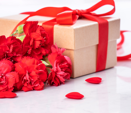 May mothers day handmade giftbox wishes photography - Beautiful blooming carnations with red ribbon bow box isolated on modern marble desk, close up, copy space, mock up Stock Photo