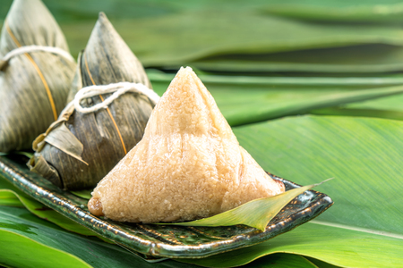 Close up, copy space, famous chinese food in dragon boat (duan wu) festival, steamed rice dumplings pyramidal shaped wrapped by bamboo leaves made by sticky rice raw ingredients