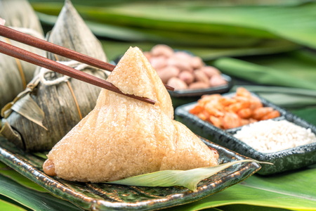 Close up, copy space, famous chinese tasty food in dragon boat (duan wu) festival, steamed rice dumplings pyramidal shaped wrapped by bamboo leaves made by sticky rice raw ingredients