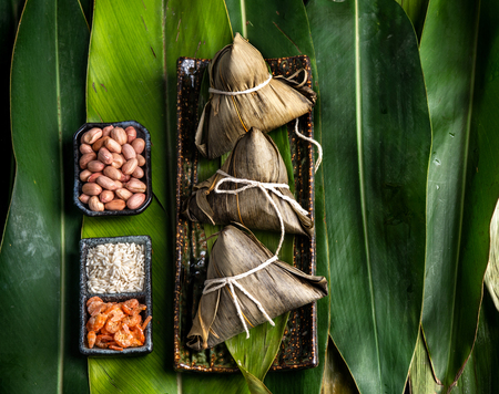 Close up, copy space, top view, famous asian chinese tasty handmade food in dragon boat(duan wu) festival, steamed rice dumplings shaped pyramidal by leaves ingredients Standard-Bild - 120841048