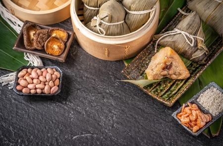 Primo piano, copia spazio, vista dall'alto, famoso cibo cinese asiatico gustoso fatto a mano nel festival della barca del drago (duan wu), gnocchi di riso al vapore a forma piramidale con ingredienti di foglie