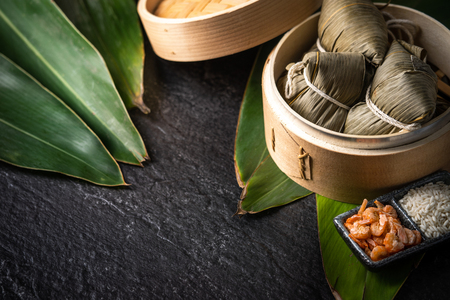Close up, copy space, top view, famous asian chinese tasty handmade food in dragon boat(duan wu) festival, steamed rice dumplings shaped pyramidal by leaves ingredients
