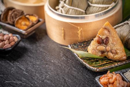 Nahaufnahme, Kopienraum, berühmtes asiatisches leckeres handgemachtes Essen im Drachenboot (Duan Wu) Festival, frisch vom Dampfer gedämpfte Reisknödel geformt pyramidenförmig umwickelt mit Blätterzutaten