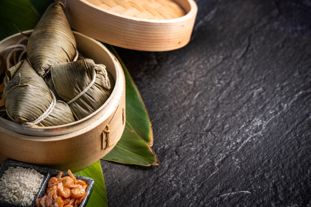 Close up, copy space, famous asian tasty handmade food in dragon boat(duan wu) festival, fresh from steamer steamed rice dumplings shaped pyramidal wrapped by leaves ingredients Reklamní fotografie
