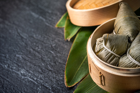 Close up, copy space, famous asian tasty handmade food in dragon boat(duan wu) festival, fresh from steamer steamed rice dumplings shaped pyramidal wrapped by leaves ingredients Zdjęcie Seryjne