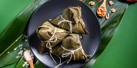 Close up, copy space, top view, flat lay. Famous asian chinese tasty handmade food in duan wu festival, steamed rice dumplings shaped like pyramidal ingredients