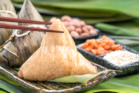 Nahaufnahme, Kopienraum, berühmtes asiatisches leckeres Essen im Drachenboot (Duan Wu) Festival, gedämpfte Reisknödel pyramidenförmig umwickelt von Bambusblättern aus klebrigen Reisrohstoffen raw Standard-Bild