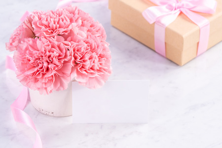 Copy space, close up, mock up, clipping path. Mothers day wording concept design. Beautiful fresh blooming baby pink color carnations isolated on bright marble background. Stock Photo