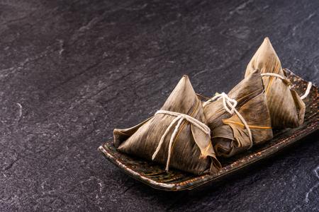 Nahaufnahme, Kopienraum, Ansicht von oben, flach. Berühmtes asiatisches chinesisches leckeres handgemachtes Essen in Duan Wu Event, gedämpfte Reisknödel in Form einer pyramidenförmigen Zutat auf schwarzem Schiefer
