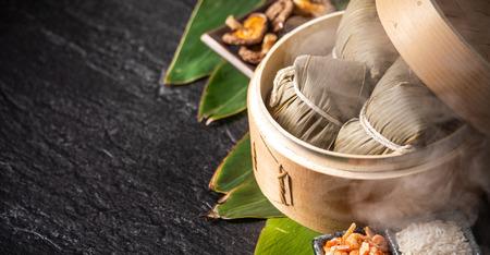 Zongzi, deliciosas albóndigas de arroz al vapor calientes frescas en vaporera. De cerca, copie el espacio, famosa comida asiática sabrosa en el festival de duanwu del barco del dragón