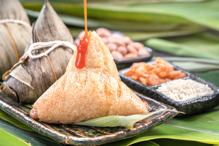 Zongzi, steamed rice dumplings with chili sauce. Close up, copy space, famous asian tasty food in dragon boat duanwu festival