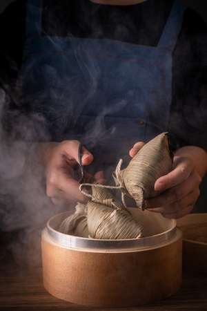 Zongzi, woman going to eat steamed rice dumpling on wood table, famous tasty food in dragon boat festival duanwu design concept, close up, copy space