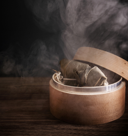 Zongzi, gnocchi di riso al vapore in piroscafo sul tavolo di legno, famoso cibo gustoso nel concetto di design duanwu del festival della barca del drago, primo piano, copia spazio.
