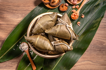 Zongzi, steamed rice dumplings on wooden table bamboo leaves, food in dragon boat festival duanwu concept, close up, copy space, top view, flat lay