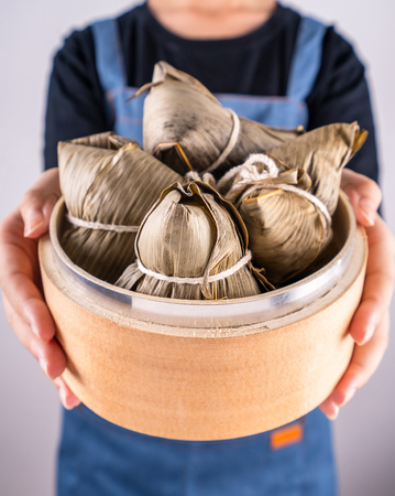 Zongzi, delicious steamed rice dumplings in steamer in black background for dragon boat festival, close up, copy space, top view, flat lay Stock Photo