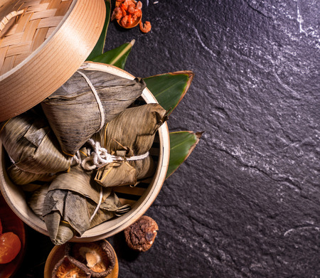 Zongzi, delicious steamed rice dumplings in steamer in black background for dragon boat festival, close up, copy space, top view, flat lay