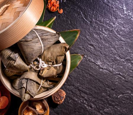 Zongzi, deliziosi gnocchi di riso al vapore in piroscafo su sfondo nero per il festival della barca del drago, primo piano, spazio copia, vista dall'alto, piatto