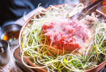 Beef barbecue bulgogi in South Korea restaurant in Seoul, lifestyle fresh korean food cuisine on copper pan with sliced grill, close up, copy space Banco de Imagens