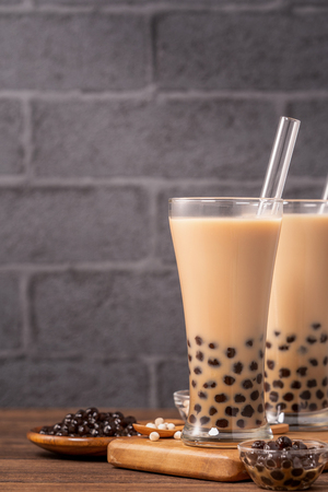 Delicious bubble milk tea with straw in drinking glass on wooden table background, concept of reduce plastic to go in Taiwan, close up, copy space