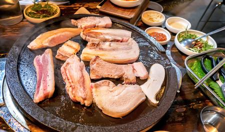Gebratenes gekochtes schwarzes Schweinefleischessen im koreanischen Restaurant, frische köstliche koreanische Küche auf Eisenplatte mit Salat, Nahaufnahme, Kopienraum, Lifestyle Standard-Bild