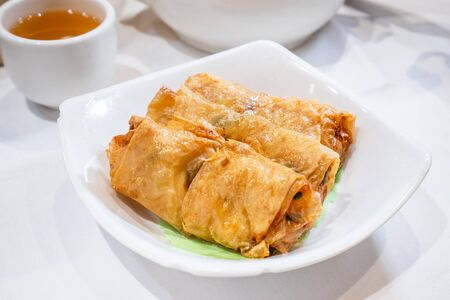 Delicious dim sum, famous cantonese food in asia - Fried bean curd (tofu skin) rolls with shrimp and prawn in hong kong yumcha restaurant, close up Stok Fotoğraf