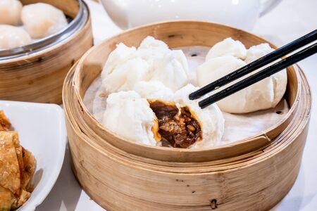 Dim sum délicieux, célèbre cuisine cantonaise en asie - Cha Siu Bao frais et chaud, petit pain de porc barbecue dans un cuiseur vapeur en bambou au restaurant yumcha de hong kong, gros plan