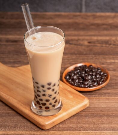 Popular Taiwan drink - Bubble milk tea with tapioca pearl ball in drinking glass and straw, wooden table gray brick background, close up, copy space