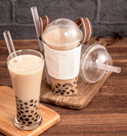 Takeout with disposable item concept popular Taiwan drink bubble milk tea with plastic cup and straw on wooden table background, close up, copy space